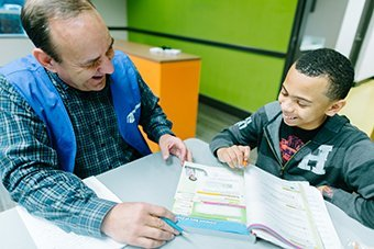 Man helping little boy who is studying